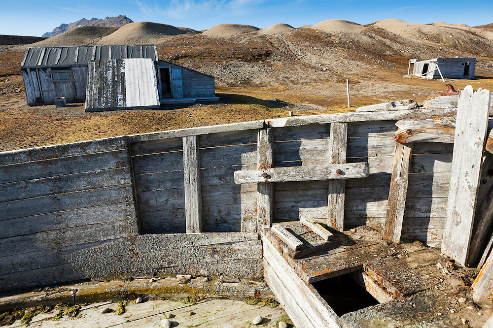 A wood barge and small structures, part of the coal mining operation erected by the British Northern Exploration Company in Calypsobyen, Svalbard in the early 1900s.
