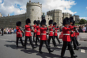 The Old Guard from the 1st Battalion Grenadier Guards leaves Windsor Castle following the Changing of the Guard ceremony on 29th July 2021 in Windsor, United Kingdom. The ceremony, which is also known as Guard Mounting, was reinstated on 22nd July for the first time since the beginning of the Covid-19 pandemic in March 2020.