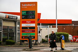 © Licensed to London News Pictures. 08/10/2021. London, UK. A woman walks past Sainsbury's petrol station in north London as Sainsbury's has increased the price of unleaded petrol and diesel by 3 pence per litre. The recent UK petrol supply crisis was caused by a shortage of HGV drivers, following the coronavirus pandemic and Brexit. Experts are predicting that motor fuel prices in the UK could reach an all-time high in the run-up to Christmas. Photo credit: Dinendra Haria/LNP