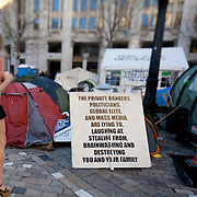 A sign berating the global elite and mass media.  The camp Occupy London Stock Exchange outside St Paul's Cathedral was in the morning served with eviction notice after months of legal battle with the Corporation of London. The site was occupied Oct 15th 2011