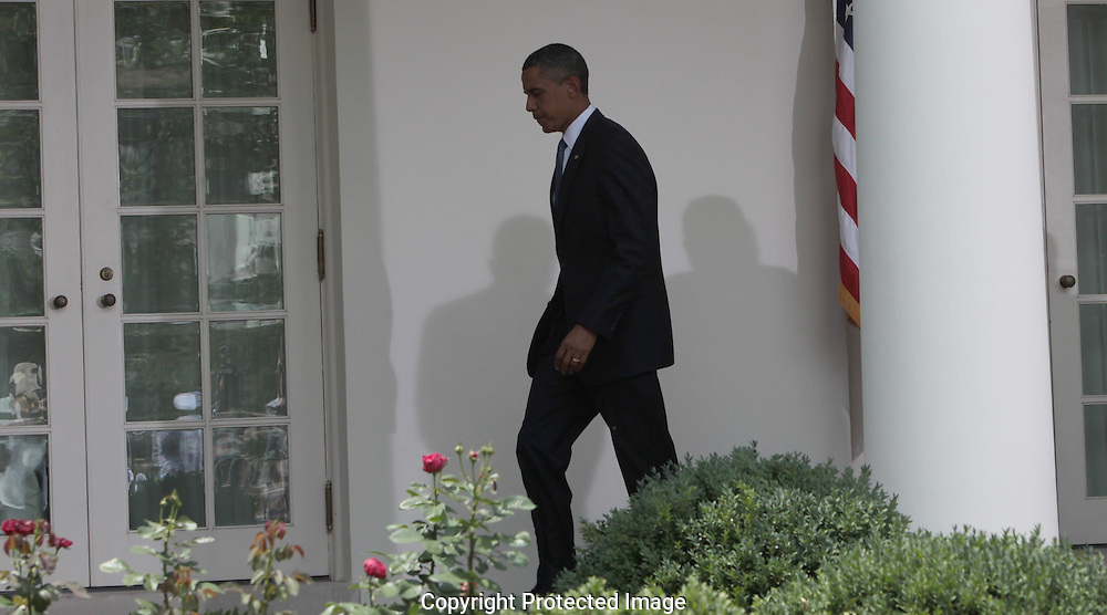 President Barack Obama walks back to the Oval Office  after announcing   the appointment of General David Petraeus to be commander of Western Forces in Afghanistan. Photograph by Dennis Brack