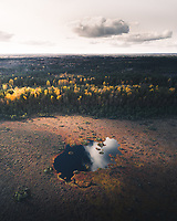 Aerial view of a small swamp surrounded by the forest  colored with the different shades of fall season in Estonia.