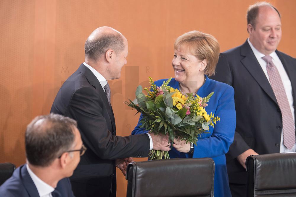 18 JUL 2018, BERLIN/GERMANY:<br /> Olaf Scholz (L), SPD, Bundesfinanzminister, ueberreicht Angela Merkel (R), CDU, Bundeskanzlerin, einen Blumenstrauss nachtraeglich zum Geburtstag, vor Beginn der Kabinettsitzung, Bundeskanzleramt<br /> IMAGE: 20180718-01-025<br /> KEYWORDS: Kabinett, Sitzung
