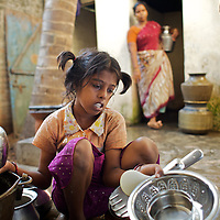 """Vijita cleans cooking utensils on the back porch of her home while her step-mother Kayalvizhi collects water...Vijita (age 14) and Vijyashree (age 11) Viswanathan lost their mother and brother to the tsunami in 2004. They continue to live in the fishing village of Thazanguda with their father Viswanathan, his second wife Kayalvizhi and their two children Sanjay (age 3) and Monica (age 1). ..Until the beginning of the 2009 academic year in June, Vijita and Vijyashree attended the local Thazanguda school. This village school teaches pupils only until the 8th Standard and with Vijita now entering the 9th, it was decided that the two daughters remain together and both travel 3km to the local town school: the Government Girls High School, Venugopalapuram in Cuddalore. ..At the same time Viswanathan decided he would cease day-to-day care of his daughters and place them in the Government Home for Tsunami Children, also in Cuddalore. This was not a move welcomed by either Vijita or Vijyashree and one afternoon after just two weeks at the orphanage, the two girls ran away. At roll call in the orphanage that evening the alarm was sounded and the two sisters were eventually located in Thazanguda waiting for their father and Kayalvizhi who were both away at the time. Realising his daughters' unhappiness, Viswanathan then took them out of the Government home. ..According to her class teacher, Vijita often compares her step-mother to her mother and concludes that she wants her mother back. Vijita confides in her teachers that her stepmother is forever demanding that she and her sister Vijyashree undertake housework. This frustration at home is tempered by the genuine love both sisters have for their father and two younger siblings Sanjay and Monica. Vijita expresses a lonelyness without her mother. Pushpavalli concludes that """"Vijita wants something else beyond the love of her father and sister"""". ..Viswanathan appears genuinely to want the best for his two elder daughters. His exp"""