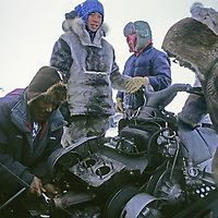 BAFFIN ISLAND, Nunavut, Canada. Inuit guides fix snowmobile in the field with simple tools & bare hands, despite subzero tempertures.