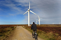 Cyclist cycling past windfarm near Halifax West Yorkshire UK