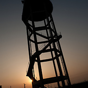 A water tower in a wheat field in Punjab. Farmers in punjab are facing problems of depleting levels of underground water that in some places is as deep as 700ft. They complain that the state government does not supply enough electricity to use the pumps. They only receive 3-5hr of electricity per day and have to use diesel generators to pump the water for their fields.