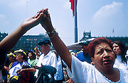 """jku032303054 - 31 JULY 2002 - MEXICO CITY, DF, MEXICO: People pray on the Zocalo in the historic center of Mexico City during a Papal mass televised to the Zocalo on large screen """"jumbotron"""" televisions. The mass, led by Pope John Paul II, was at the Basilica of Guadalupe in Mexico City, July 31, 2002. The Pontiff, making his fifth trip to Mexico, canonized Juan Diego, the Mexican Indian who first saw the image of the Virgin of Guadalupe in 1531. Juan Diego is now known at Saint Juan Diego. PHOTO © JACK KURTZ  RELIGION  INDIGENOUS  CULTURE  PATRIOTISM"""