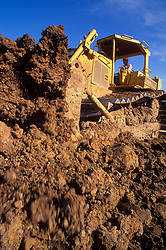 Stock photo of a man moving piles of dirt with a bulldozer at a construction site