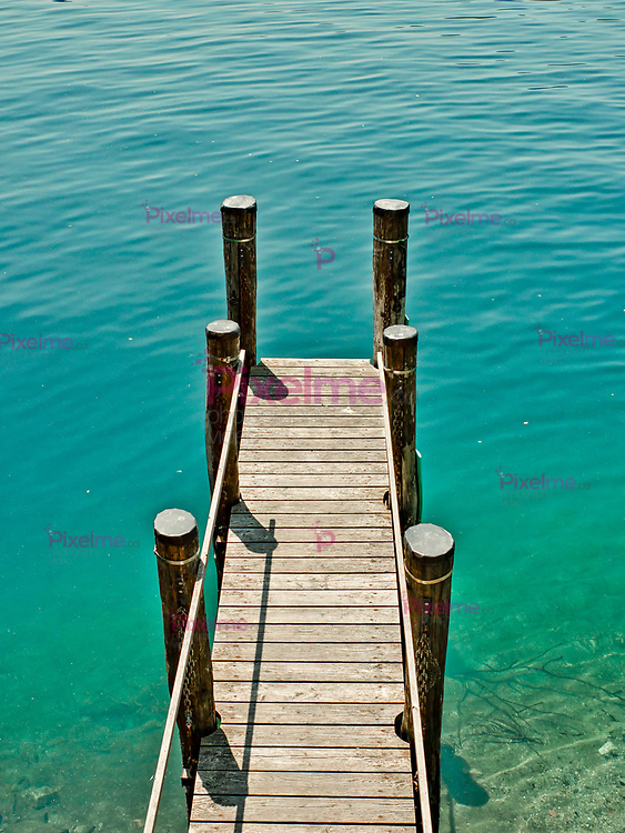 Wooden pier surrounded by water on the lake orta italy during a summer afternoon