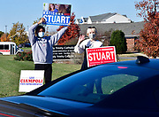 Fernando Jimenez of Collinsville (left) and Katharine Earnest of Alton wave at voters turning into the parking lot of Holy Trinity Catholic Church in Fairview Heights on Tuesday November 3, 2020. The were by the roadway, well away from the polling place entrance to avoid any electioneering issues, as they waved to cars and held signs for Katie Stuart, who is running for re-election as state representative in the 112th district. In the ground at left is a sign for Lisa Ciampoli, who is challenging Stuart.<br /> Photo by Tim Vizer