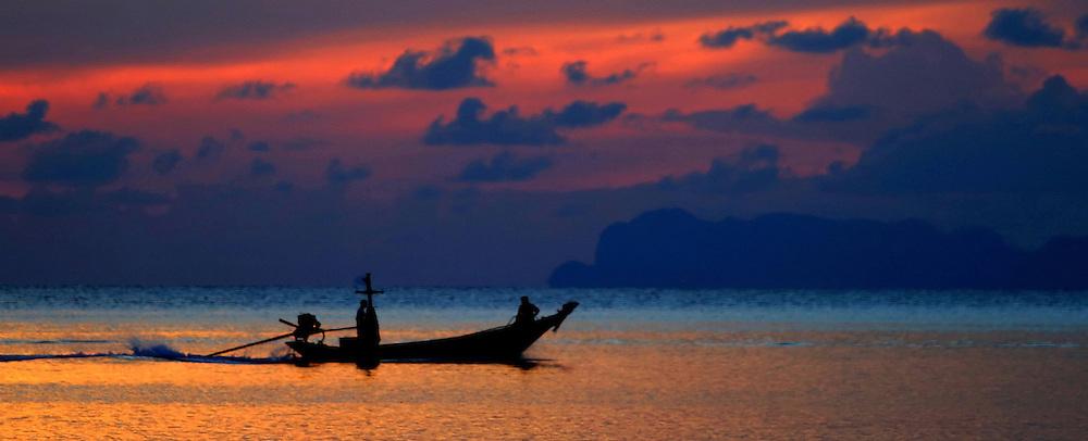 Long tail boat at sun set Koh Phangan Thailand