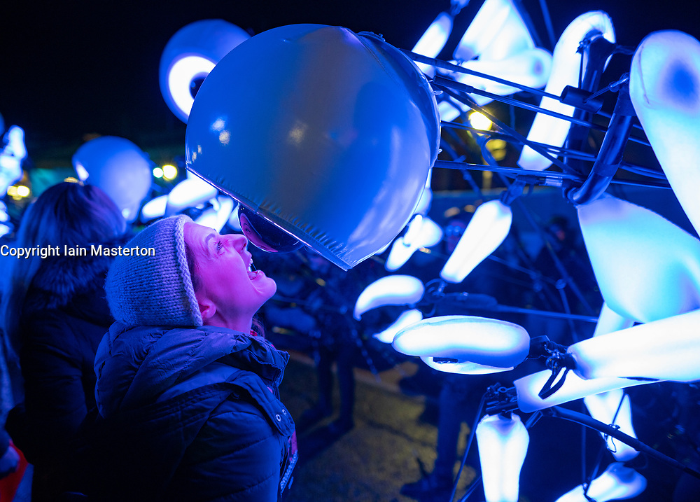 Edinburgh, Scotland, UK. 31st Dec 2019. Edinburgh's famous Hogmanay party. Pictured, street party guest gets close to high-tech puppet from Close-Act Theatre from the Netherlands. Iain Masterton/Alamy Live News
