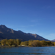 A Yacht moored in the pristine waters of Lake Wakatipu at Glenorchy in Autumn..Glenorchy is a small settlement nestled in spectacular scenery at the northern end of Lake Wakatipu in New Zealand's south Island. It is approximately 45 kilometres by road or boat from Queenstown, the nearest large town..Glenorchy is a popular tourist spot, close to many tramping tracks. It lies near the borders of Mount Aspiring National Park and Fiordland National Park. The local scenery received worldwide attention when it was used as one of the settings in the first of Peter Jackson's Lord of the Rings films. Glenorchy is the home of  Dart River Jet Safaris. The  unique adventure combines exhilarating wilderness jet boating with unique Funyak inflatable canoes used to explore the magnificent World Heritage wilderness within Mt Aspiring National Park. Professional guides take participants through dramatic landscapes, paddling along channels of the glacier fed Dart River's braided river system as well as along hidden side streams, rock pools and dramatic chasms. Glenorchy, New Zealand. 13th April 2011. Photo Tim Clayton..