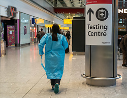 © Licensed to London News Pictures. 17/01/2021. London, UK. A woman in a medical gown walks past a Testing Centre sign at London Heathrow. Passengers arriving from abroad on Monday morning will have to show that they have had a negative Covid-19 test. Today, Foreign Secretary Dominic Rabb, said that lockdown could be lifted in March but with tier systems in place as health chiefs reveal that a 24/7 vaccination pilot will begin next week as total Covid-19 deaths reach over 88,000 this weekend. Photo credit: Alex Lentati/LNP