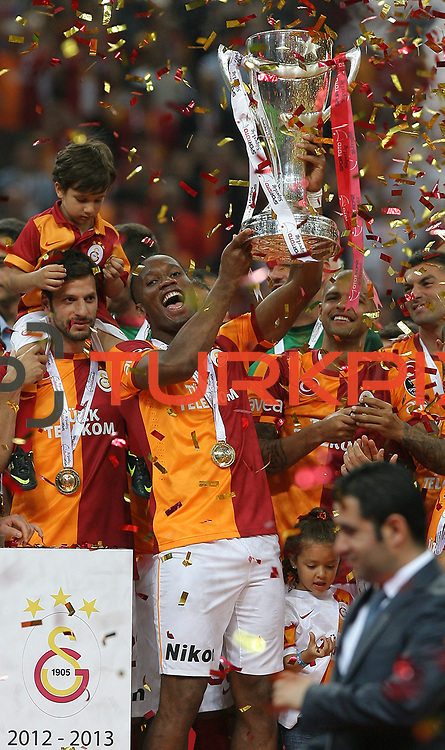 Galatasaray players Didier Drogba celebrate with the trophy after their Turkish Super League soccer match against Trabzonspor at Turk Telekom Arena stadium May 18, 2013.Galatasaray won the Turkish league title for the 19th time. Photo by TURKPIX