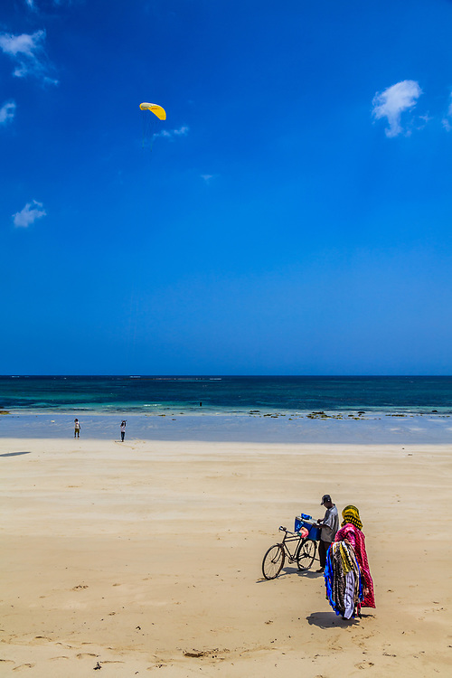 Lesso sellers are watching kite flying at Diani Beach, Kenya.
