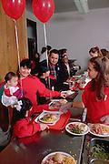 Teen serving family Christmas dinner in church soup kitchen.  Minneapolis Minnesota USA