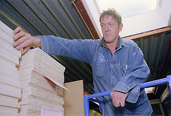 Man with disability checking materials in warehouse,