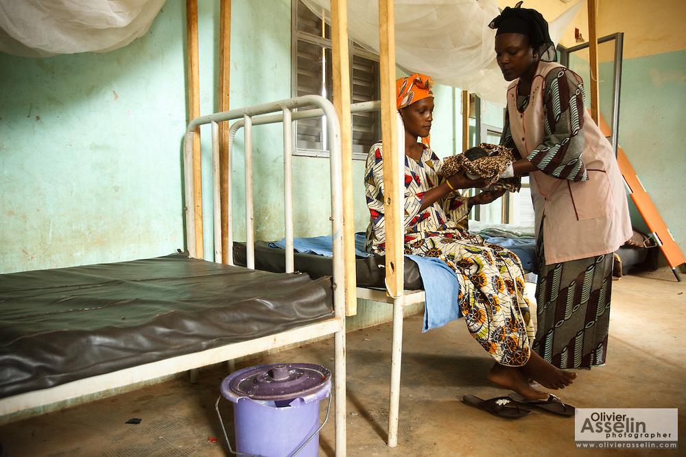 Midwife Dagnoko Alima Dambele hands her newborn child to Mariam Keita, 20, at the Badegna community health center in the town of Kita, Mali on Sunday August 29, 2010.