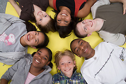 Group of teenagers lying in a circle,