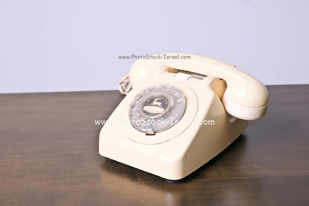 Cutout of a retro ivory coloured telephone on white background