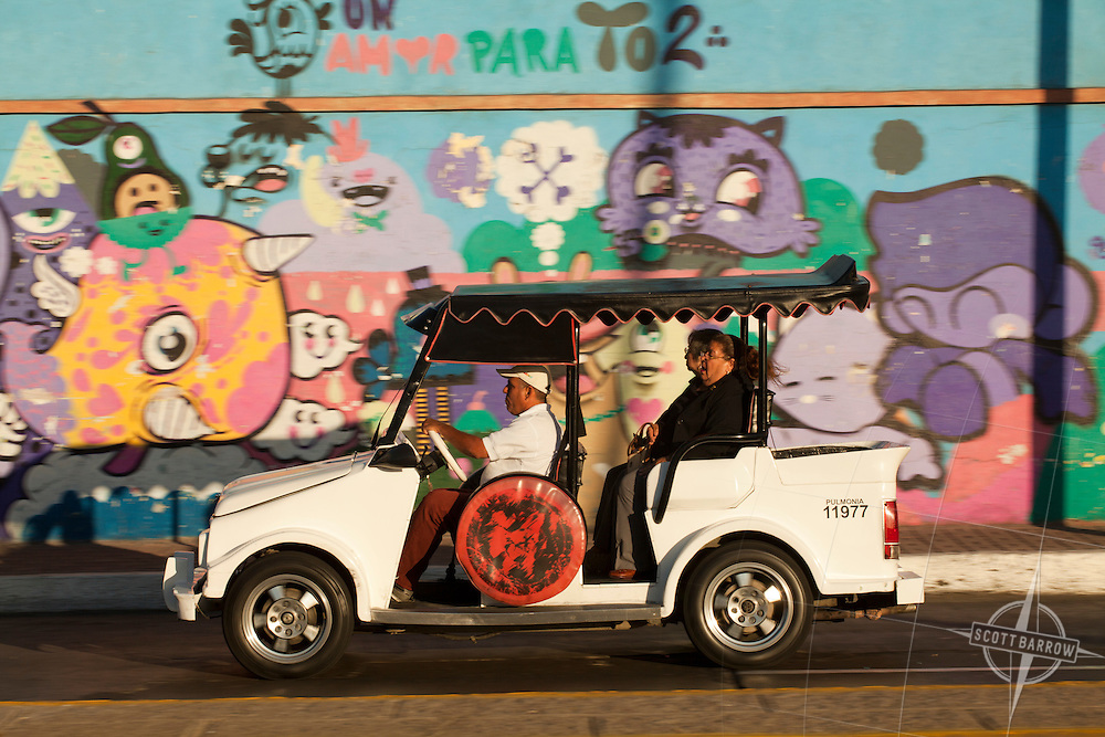 Pulmonia taxi in Mazatland, Mexico with colorful, painted wall.