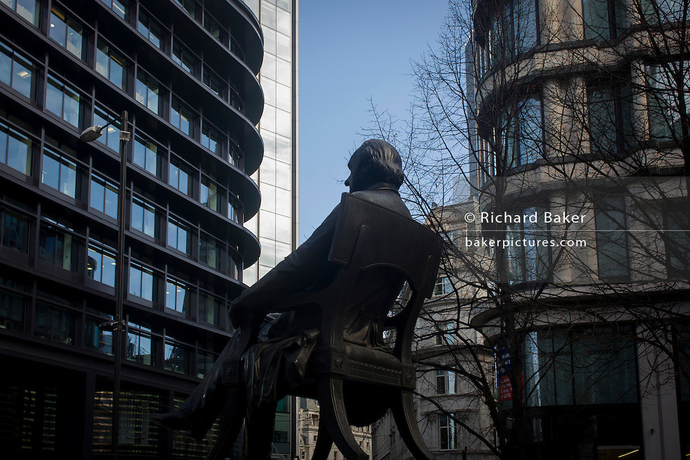 The rear of the statue of George Peabody and modern offices in the heart of the financial City of London. Peabody was a philanthropist, banker and entrepreneur George Peabody (1795 to 1869). The three men each concentrate on their own communications, all separated by a suitable personal space to maintain their privacy. The pavement is a pedestrian area near the Bank of England and adjacent to the 3rd Royal Exchange built in 1842 by Sir William Tite. .