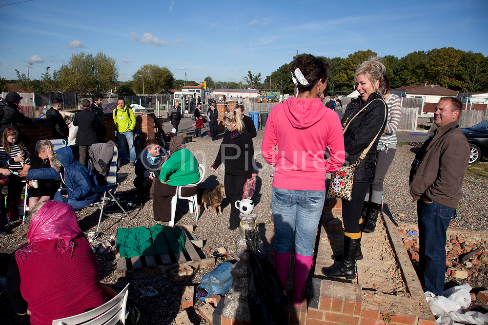 Travellers sit around a fire chatting and waiting for developments at Dale Farm site prior to eviction. Riot police and bailiffs were present on 20th October 2011, as the site was cleared of the last protesters chained to barricades. Dale Farm is part of a Romany Gypsy and Irish Traveller site in Crays Hill, Essex, UK<br /> <br /> Dale Farm housed over 1,000 people, the largest Traveller concentration in the UK. The whole of the site is owned by residents and is located within the Green Belt. It is in two parts: in one, residents constructed buildings with planning permission to do so; in the other, residents were refused planning permission due to the green belt policy, and built on the site anyway.