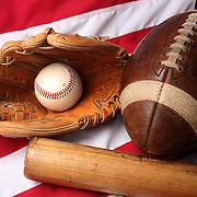 A studio shot of an American Football and baseball ball glove and bat on an American flag. 17th October 2012. Photo Tim Clayton