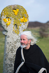 © Licensed to London News Pictures. 05/03/2017. PERRANPORTH, CORNWALL, UK.  St Piran next to the ancient stone cross. St. Piran's Day in Cornwall. St Piran is the patron Saint of Sinners in Cornwall and it is his flag that is recognised as the Cornish flag. Today his arrival from Ireland to Cornwall is celebrated across Cornwall especially in Perranporth where it is believed that he landed. He set up an Oratory and a Church the remains of which have been recently uncovered in the sand dunes at Perranporth..  Photo credit: MARK HEMSWORTH/LNP