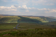 View from Swaledale, which runs broadly from west to east. To the south and east of the ridge a number of smaller dales. Swaledale is a typical limestone Yorkshire dale, with its narrow valley-bottom road, green meadows and fellside fields, white sheep and dry stone walls on the glacier-formed valley sides, and darker moorland skyline. Yorkshire, England, UK. This is a farming area where rural living in the countryside is at the centre of life in this Northern county.
