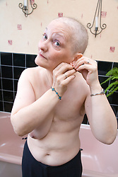 Woman who has had a mastectomy; the removal of a breast in response to breast cancer; looking in the mirror to put on earrings in her bathroom,