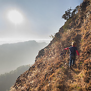 Child runs up a steep hill in sunset.