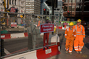 Real passing construction workers and a scaled human workman figure who warns pedestrians to stay on established footpath, and not wander into construction site roadways during street improvements in Victoria, central London.