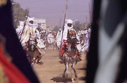 Local chiefs ride horses towards the Emir to pay homage to him, during the Durbar Fantasia..The Durbar Fantasia, is the moment where The Husa residents of Kano wear traditional dress, their local leaders and chiefs mount horses, and together with their militias display allegiance and homage to their leader, the Emir of Kano. This takes place after Ramadan. The Emir is Kano's State official political and economic feudal leader, everyone seeks to be in his pleasure, otherwise they reap the consequences..Kano is the largest Muslim Husa city, under the feudal, political and economic rule of the Emir. Kano and the other eleven northern states are under Islamic Sharia Law which is enforced by official state apparatus including military and police, Islamic schools and education, plus various volunteer Militia groups supported financially and politically by the Emir and other business and political bodies. 70% of the population live below the poverty line. Kano, Kano State, Northern Nigeria, Africa