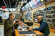 A male customer looks as a camera with a males sales assistant in B&H professional camera shop on 420 9th Avenue, New York City, New York, United States of America.