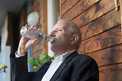 Senior businessman drinking water from a bottle, Freiburg im Breisgau, Baden-Wuerttemberg, Germany