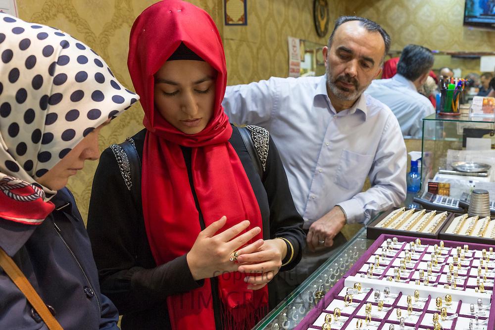 Muslim woman with  gold ring in jewelry shop in The Grand Bazaar, Kapalicarsi, great market, Beyazi, Istanbul, Turkey