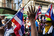 05 JANUARY 2014 - BANGKOK, THAILAND: A supporter of the anti-government movement waves to protestors passing her on the street in Bangkok. Suthep Thaugsuband, leader of the anti-government protests in Bangkok, led the protestors on a march through the Chinatown district of Bangkok. Tens of thousands of people waving Thai flags and blowing whistles gridlocked what was already one of the most congested parts of the city. The march was intended to be a warm up to their plan by protestors to completely shut down Bangkok starting Jan. 13.     PHOTO BY JACK KURTZ