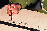 China Yunnan province Lijiang Man in traditional clothes doing Calligraphy as a tourist entertainment