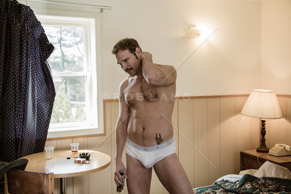 hot man in his underwear standing in a motel room with a bottle of Jack Daniels in his hand