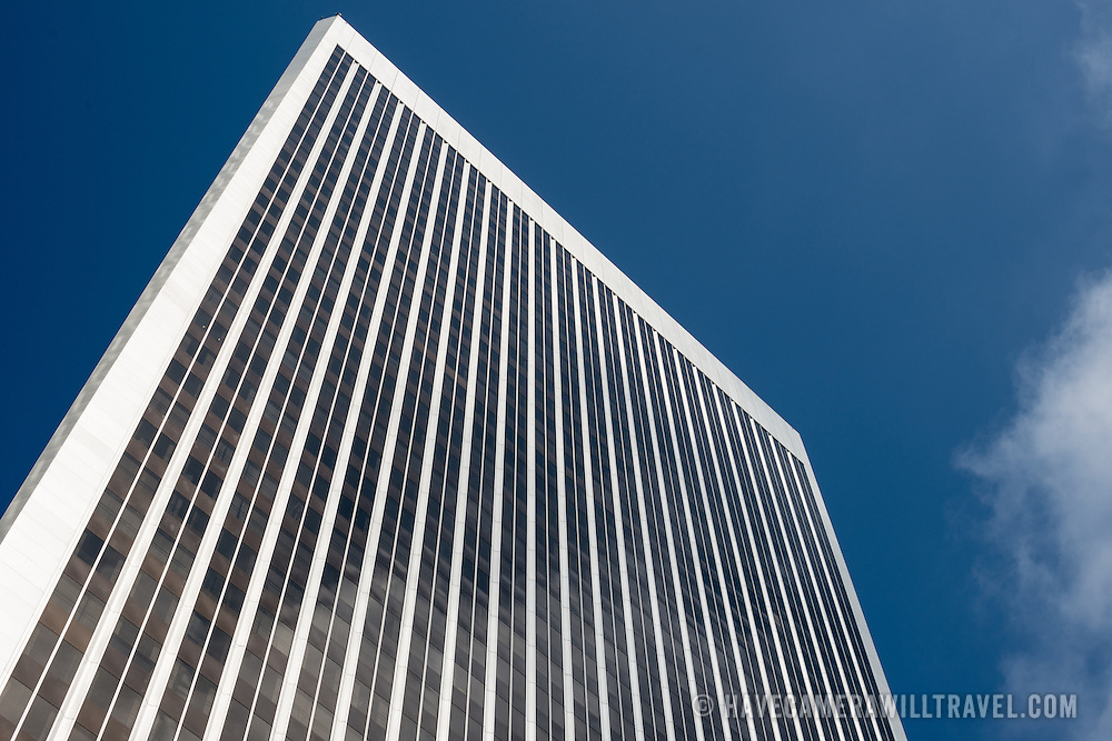 Looking up at a modern office building against a mostly clear blue sky, with a few wispy clouds at right of frame.