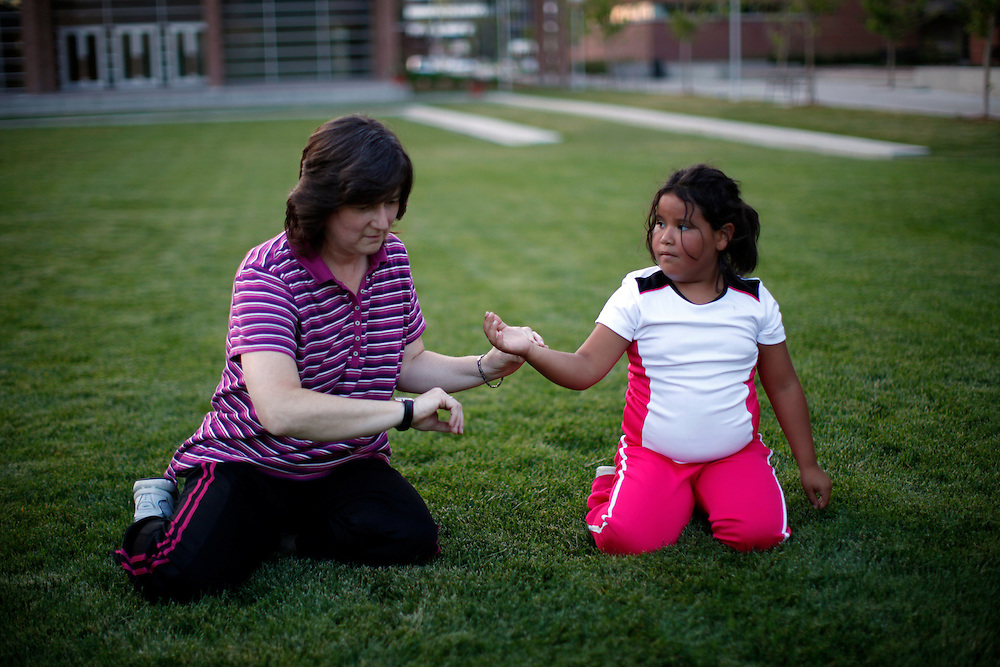 Recreation Therapist Beckie Joyce (L) takes the pulse of Fernanda Garcia-Villanueva after  group exercise in the 10-week Shapedown Program at The Children's Hospital in Aurora, Colorado May 29, 2010.  The program is part of the child and teen weight management program at the hospital. REUTERS/Rick Wilking (UNITED STATES)