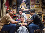 "25 MAY 2015 - BANGKOK, THAILAND: VANESSA, an American visitor to Thailand,  gets a Sak Yant tattoo from AJARN NENG ONNUT. Sak Yant (Thai for ""tattoos of mystical drawings"" sak=tattoo, yantra=mystical drawing) tattoos are popular throughout Thailand, Cambodia, Laos and Myanmar. The tattoos are believed to impart magical powers to the people who have them. People get the tattoos to address specific needs. For example, a business person would get a tattoo to make his business successful, and a soldier would get a tattoo to help him in battle. The tattoos are blessed by monks or people who have magical powers. Ajarn Neng, a revered tattoo master in Bangkok, uses stainless steel needles to tattoo, other tattoo masters use bamboo needles. The tattoos are growing in popularity with tourists, but Thai religious leaders try to discourage tattoo masters from giving tourists tattoos for ornamental reasons.       PHOTO BY JACK KURTZ"