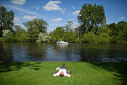 © London News Pictures. 15/05/2016. Windsor, UK. A lone man lying on the banks of the River Thames in warm sunshine on the final day of the 2016 Royal Windsor Horse Show, held in the grounds of Windsor Castle in Berkshire, England. This years event is part of HRH Queen Elizabeth II's 90th birthday celebrations.  Photo credit: Ben Cawthra/LNP