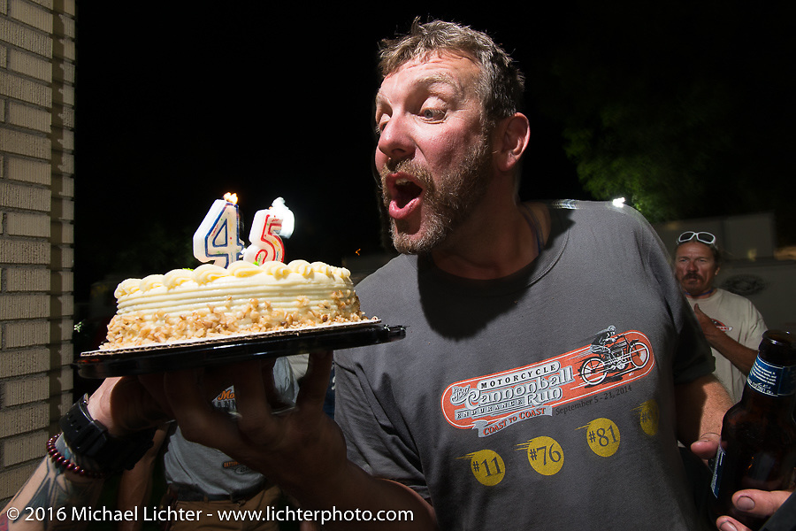 """Robert """"Big Swede"""" Gustavsson gets a birthday cake at his parking lot Pizza Party from host Dean """"Dino"""" Bordigioni after stage 12 (299 m) of the Motorcycle Cannonball Cross-Country Endurance Run, which on this day ran from Springville, UT to Elko, NV, USA. Wednesday, September 17, 2014.  Photography ©2014 Michael Lichter."""