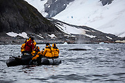 Tourists on a rubber dinghy boat whale watching near an iceberg. Photographed in Paradise Bay, Antarctica.