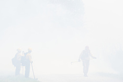 Firefighters working in smoke controlled burn on the Matthews Prairie, owned by the Native Prairies Association of Texas. Farmersville, Texas, USA.