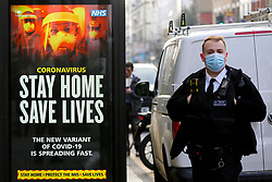 "© Licensed to London News Pictures. 09/01/2021. London, UK. A police officer wearing a protective face covering walks past the Government's ''Stay Home, Save Lives' Covid-19 publicity campaign poster in north London, as the number of cases of the mutated variant of the SARS-Cov-2 virus continues to spread around the country. The message in the advertising campaign post says 'The new variant of Covid-19 is spreading fast'. Prime Minister Boris Johnson has said that the public should ""stay at home"". Police officers have power to fine people if they break the restrictions by not staying at home. Photo credit: Dinendra Haria/LNP"